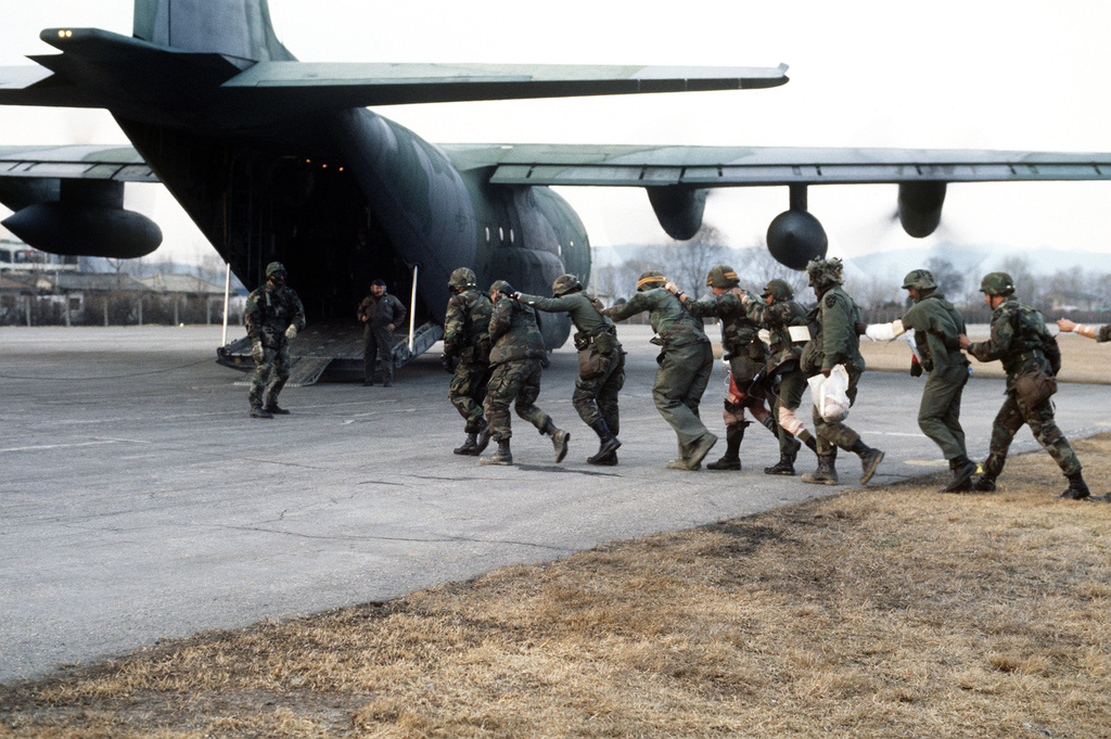 """Ambulatory""""casualties""""file across the flight line into a C-130 Hercules aircraft while being evaluated during Exercise TEAM SPIRIT'86"""