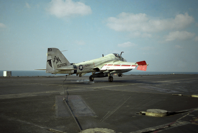 An A-6E Intruder aircraft engages an arresting cable while landing aboard the aircraft carrier USS SARATOGA (CV 60)