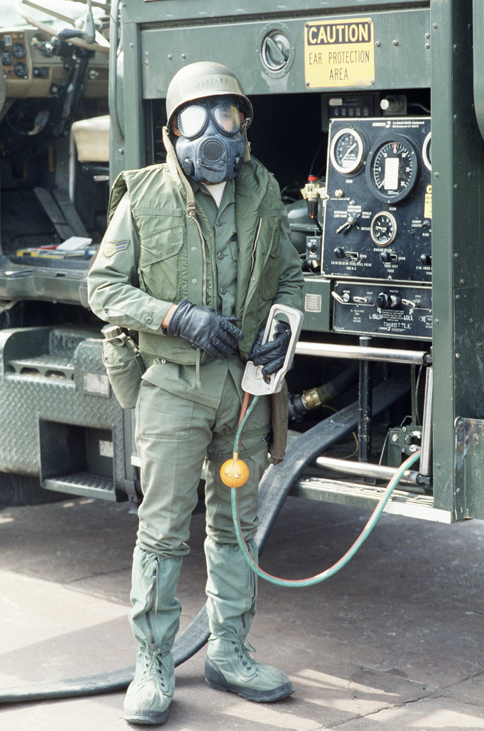 An AIRMAN in chemical-biological warfare gear stands by the control panel of a fuel truck during Exercise TEAM SPIRIT'86