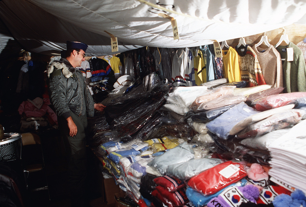 """Captain (CPT) Hurshel Wade, 21st Tactical Air Support Squadron, shops for clothing at the""""tent city""""concession arcade during Exercise TEAM SPIRIT'86"""