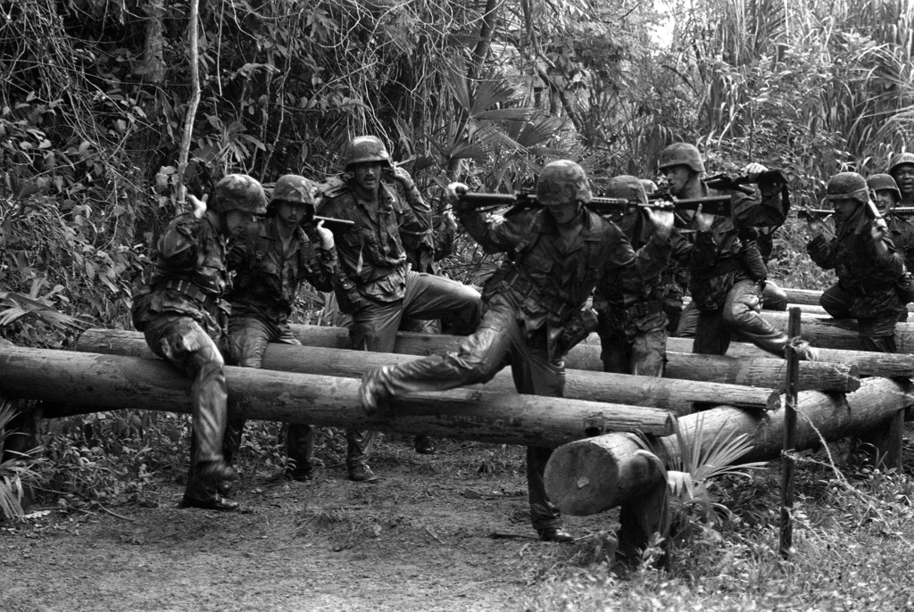 """Members of the 1ST Battalion, 5th Marines, negotiate a log obstacle on the """"Green Hell"""" obstacle course during a jungle operations training course"""