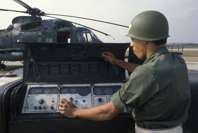 Sergeant (SGT) Keith Gray Jr., a turboprop engine technician with the 31st Aerospace Rescue and Recovery Squadron, adjusts a generator while servicing an HH-3E Jolly Green Giant helicopter during Exercise TEAM SPIRIT'86
