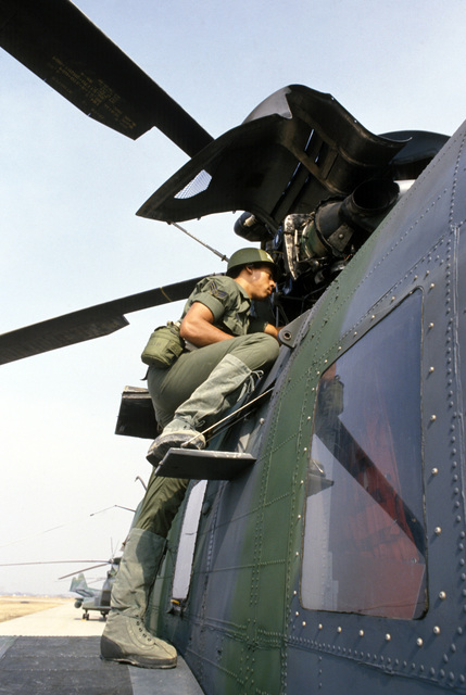 Sergeant (SGT) Keith Gray Jr., a turboprop engine technician with the 31st Aerospace Rescue and Recovery Squadron, services an HH-3E Jolly Green Giant helicopter during Exercise TEAM SPIRIT'86
