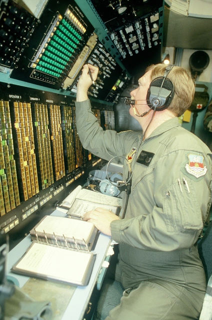 Technical Sgt. Ken Clover, 7th Airborne Command and Control Squadron, sets the frequency position on a communication monitor inside an EC-130E Hercules airborne battlefield command and control center aircraft during exercise Team Spirit '86