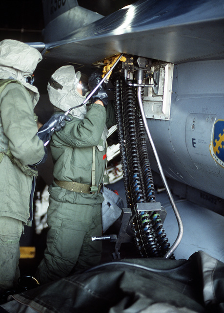 US Air Force personnel in chemical-biological warfare gear load 20 mm rounds into an F-16 Fighting Falcon aircraft during Exercise TEAM SPIRIT'86