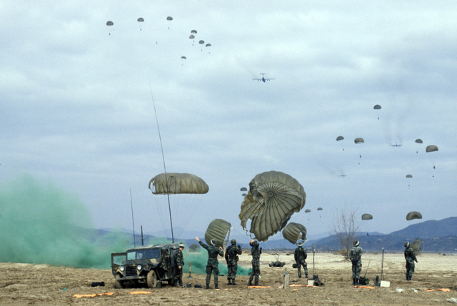 US Army and Korean paratroopers drop over the Yoju airstrip during Exercise TEAM SPIRIT'86.  Members of Detachment 1, 122nd Combat Control Squadron, foreground, have set up a perimeter and demarcated the landing zone