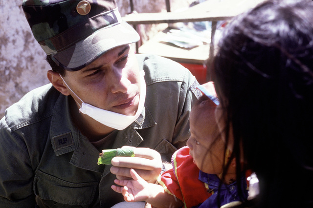 Lieutenant (Dr.) Eric Martinez from Panamanian Defense Force teaches a villager how to use a Chumico leaf to clean teeth during a humanitarian aid operation for impoverished Panamanians