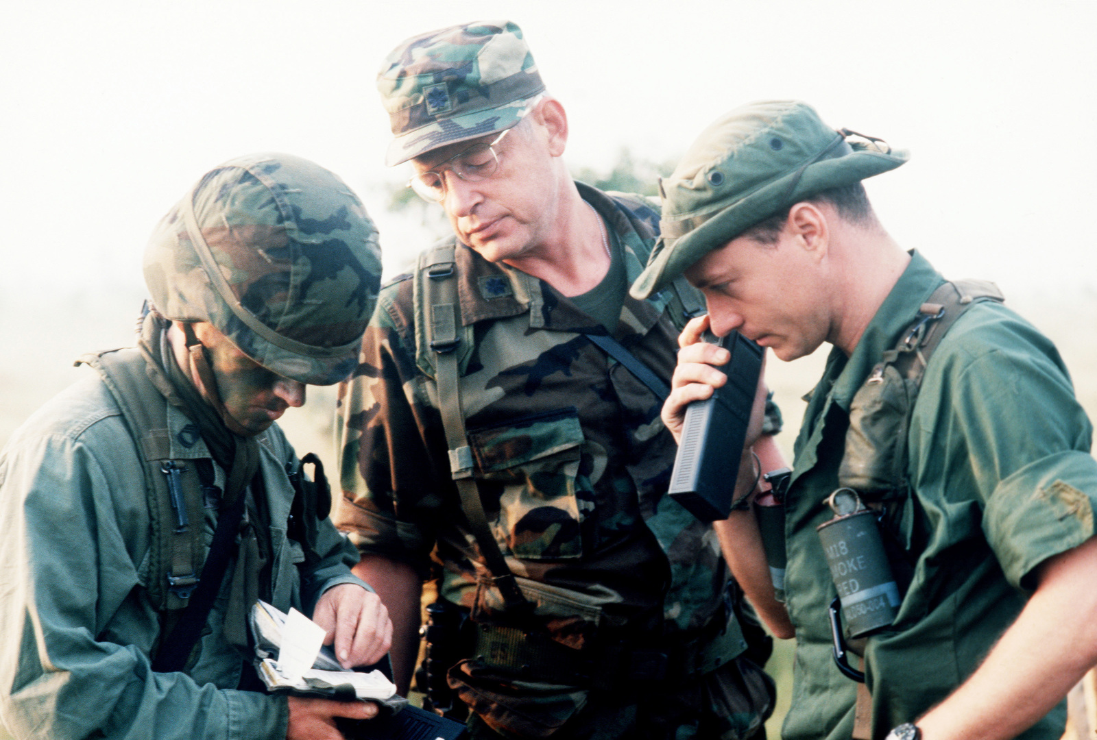 Sergeant (SGT) Shaw, left, of the 27th Engineering Battalion; Lieutenant Colonel (LTC) Williams, the Military Airlift Command representatives; and Captain (CPT) Card, 317th Combat Control Team, discuss details of the airdrop during Exercise CABANAS '86