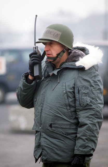 Colonel (COL) Thomas O. Hansen, commander, 435th Combat Support Group, coordinates efforts by a 435th Explosive Ordnance Disposal team to defuse a suspected car bomb outside the Military Airlift Command passenger terminal. After further investigation, it was determined that the car did not contain a bomb