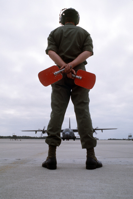 A plane director prepares to signal taxiing instructions to a 16th Special Operations Squadron AC-130H Hercules gunship aircraft. The aircraft is armed with a 105 mm Howitzer and a 40 mm cannon