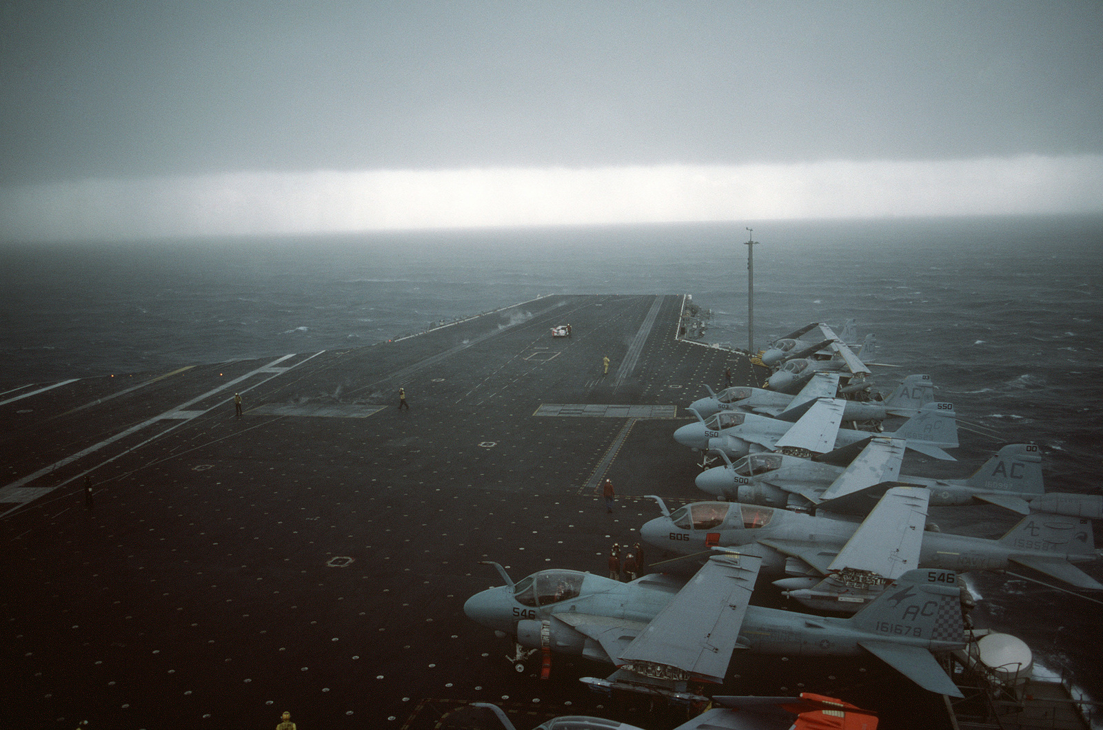 A storm approaches the aircraft carrier USS JOHN F. KENNEDY (CV 67). Parked on the flight deck are several A-6E Intruder aircraft and an EA-6B Prowler aircraft
