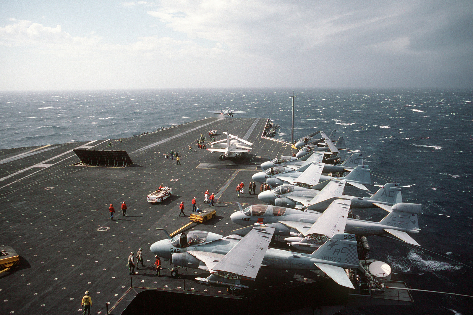 An F-14A Tomcat aircraft is launched from the aircraft carrier USS JOHN F. KENNEDY (CV 67) as an S-3A Viking aircraft is attached to the catapult on the right. Six A-6E Intruder aircraft and an EA-6B Prowler aircraft are parked on the deck edge