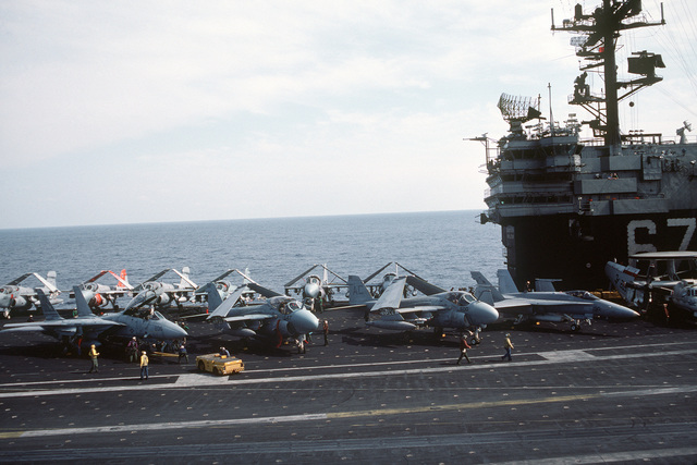 Flight deck crewmen prepare to tow an F-14A Tomcat aircraft from Fighter Squadron 32 (VF-32) with an MD-3A tow tractor during flight operations board the aircraft carrier USS JOHN F. KENNEDY (CV 67). Aircraft parked on the flight deck include A-6E Intruders, EA-6B Prowlers, and F/A-18A Hornet and an E-2C Hawkeye