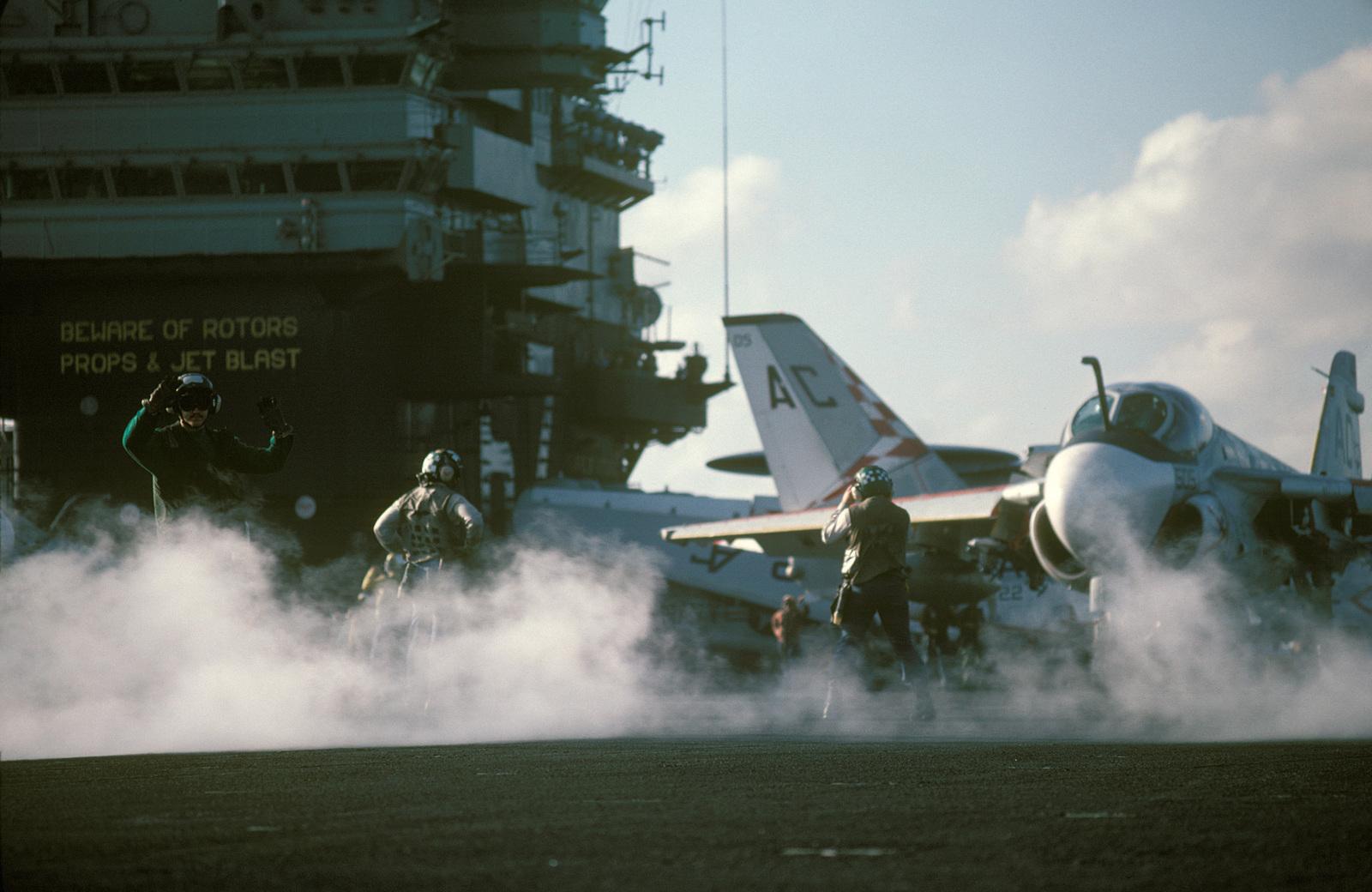 Steam drifts across the flight deck as an A-6E Intruder aircraft is prepared for launch from the aircraft carrier USS JOHN F. KENNEDY (CV 67)