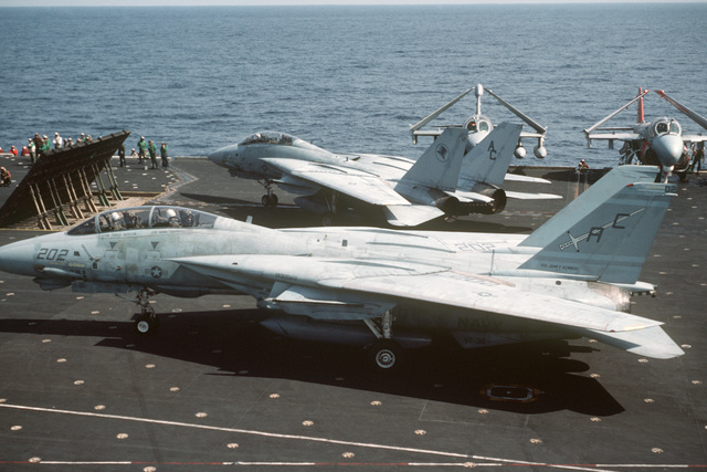 Two F-14A Tomcat aircraft taxi on the flight deck behind a jet blast deflector during flight operations aboard the aircraft carrier USS JOHN F. KENNEDY (CV 67). The aircraft in the foreground is from Fighter Squadron 32 (VF-32) and the aircraft in the background is from Fighter Squadron 14 (VF-14)