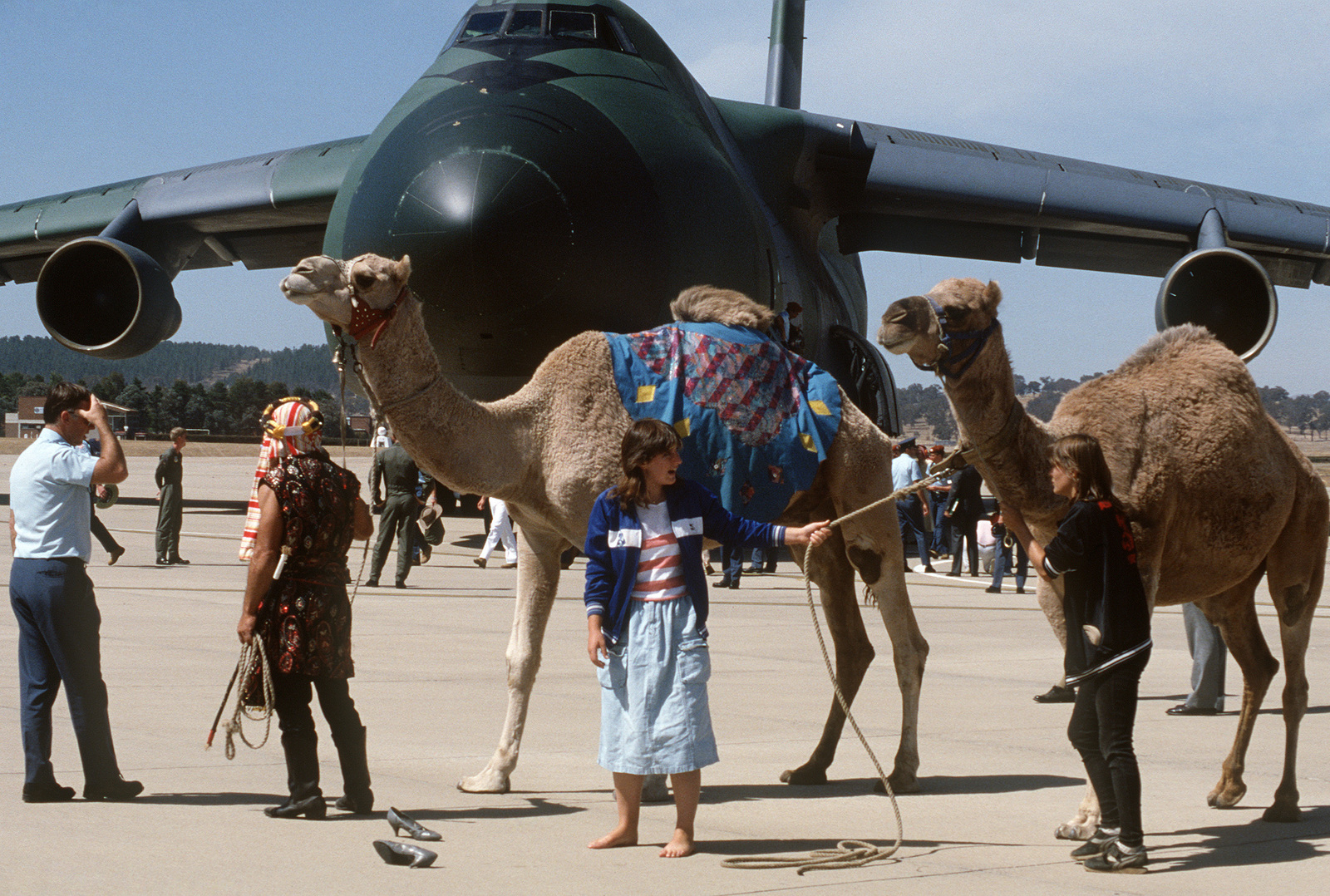 Circus members with camels welcome Australian troops upon their arrival at  the Fairbairn air force base