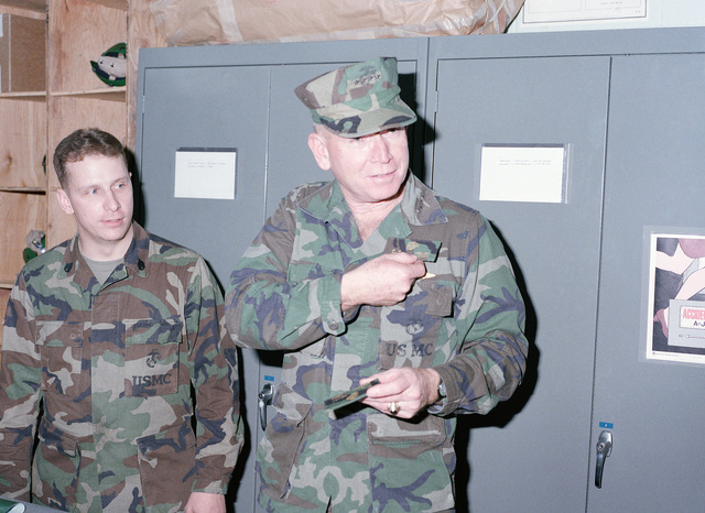 General (GEN) P.X. Kelley, commandant of the Marine Corps, receives his flying name tag from STAFF Sergeant (SSGT) Wilson, Marine Aerial Refueler Transport Squadron 152 (VMGR-152), during the general's visit to the base
