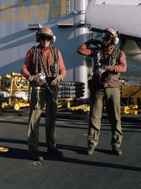 Flight deck crewman carry aircraft tiedown lines aboard the nuclear-powered aircraft carrier USS CARL VINSON (CVN-70)