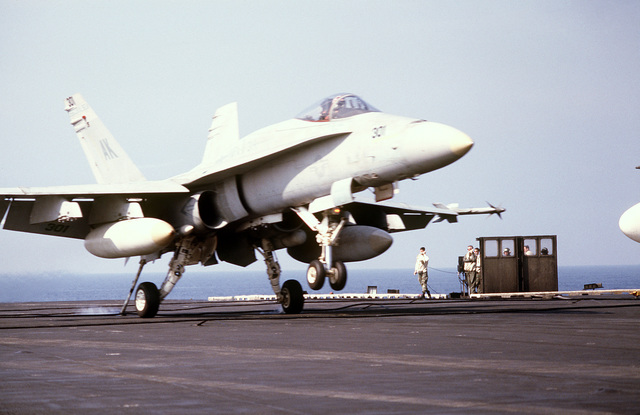 An F/A-18A Hornet aircraft from Marine Fighter Attack Squadron 314 (VMFA-314) lands aboard the aircraft carrier USS CORAL SEA (CV-43) during flight operations off the coast of Libya. The aircraft is armed with AIM-9 Sidewinder missiles on the wing tips