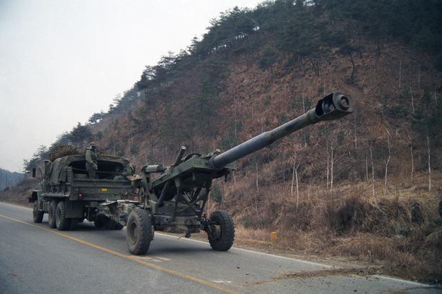 An M198 155 mm Howitzer of the 1ST Battalion, 8th Field Artillery Regiment, 25th Infantry Division, is towed along Highway 44 by an M923 5-ton truck during the joint US/Korean Exercise TEAM SPIRIT '86