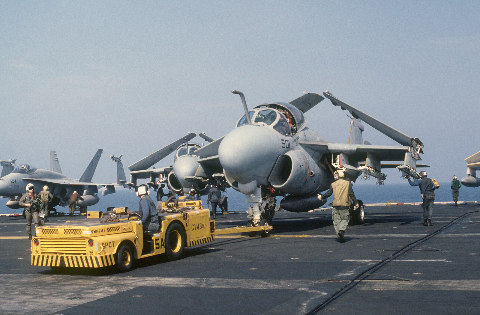 An MD-3A tow tractor is used to park an A-6E Intruder aircraft on the flight deck aboard the aircraft carrier USS CORAL SEA (CV 43) during flight operations off the coast of Libya
