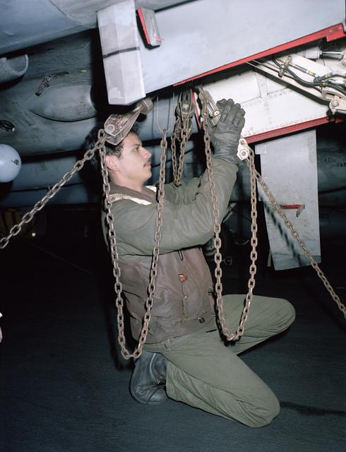 A crew member aboard the aircraft carrier USS SARATOGA (CV 60) attaches tie-down chains to the underside of an aircraft to prevent damage during high seas
