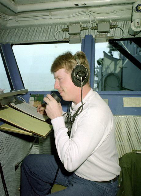 A crewman aboard the aircraft carrier USS SARATOGA (CV-60) lists the names of personnel on a manning roster while communicating through a sound-powered telephone in the primary flight control station