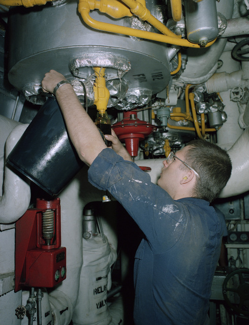 A fireman aboard the aircraft carrier USS SARATOGA (CV 60) takes a sample of oil to be tested in the oil laboratory aboard ship