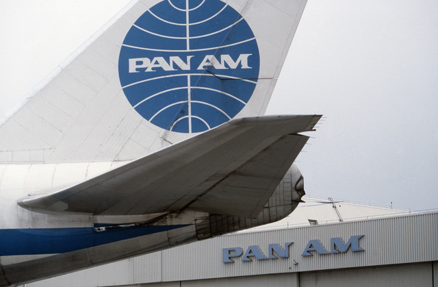 A left side view of the tail section of a Boeing 747 aircraft with Pan Am hangar 19 visible in the background. The aircraft is undergoing modification as part of a Military Airlift Command plan to use 115 Boeing and McDonnell Douglas jetliners as air ambulances in the event of war. The aircraft, which would be part of the Civil Reserve Air Fleet, would airlift patients back to the United States