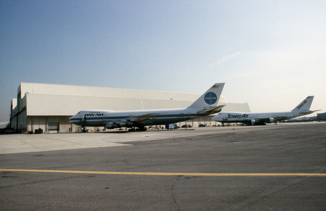 A left side view of two Boeing 747 aircraft parked beside Pan Am hangar 19. The aircraft are undergoing modification as part of a Military Airlift Command plan to use 115 Boeing and McDonnell Douglas jetliners as air ambulances in the event of war. The aircraft, which would be part of the Civil Reserve Air Fleet, would airlift patients back to the United States