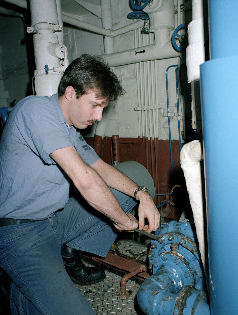 A machinist's mate adjusts fittings in an engineering space aboard the aircraft carrier USS SARATOGA (CV 60)