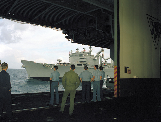Crewmen watch from a hangar bay aboard the aircraft carrier USS SARATOGA (CV 60) as the fast combat support ship USS SEATTLE (AOE 3) comes alongside for an underway replenishment during operations off the coast of Libya