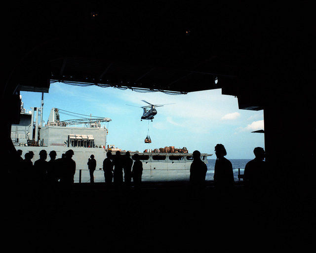 Crewmen watch from a hangar bay aboard the aircraft carrier USS SARATOGA (CV 60) as a A CH-46 Sea Knight helicopter approaches with a load of supplies from the fast combat support ship USS SEATTLE (AOE -3) during a vertical replenishment operation. The ships are operating off the coast of Libya