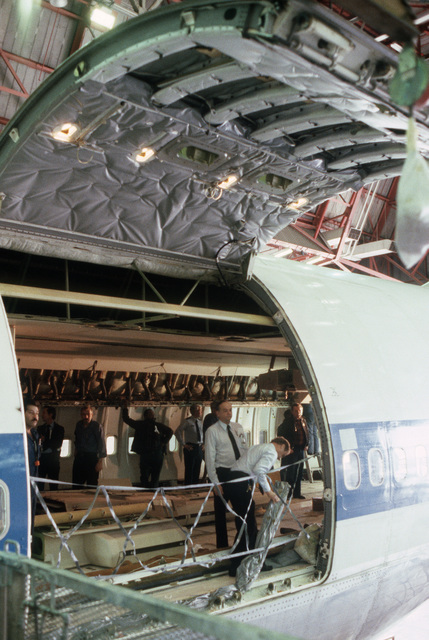 Technicians inspect alterations to the cargo door of a Boeing 747 aircraft. The aircraft is undergoing modification as part of a Military Airlift Command plan to use 115 Boeing and McDonnell Douglas jetliners as air ambulances in the event of war. The aircraft, which would be part of the Civil Reserve Air Fleet, would airlift patients back to the United States