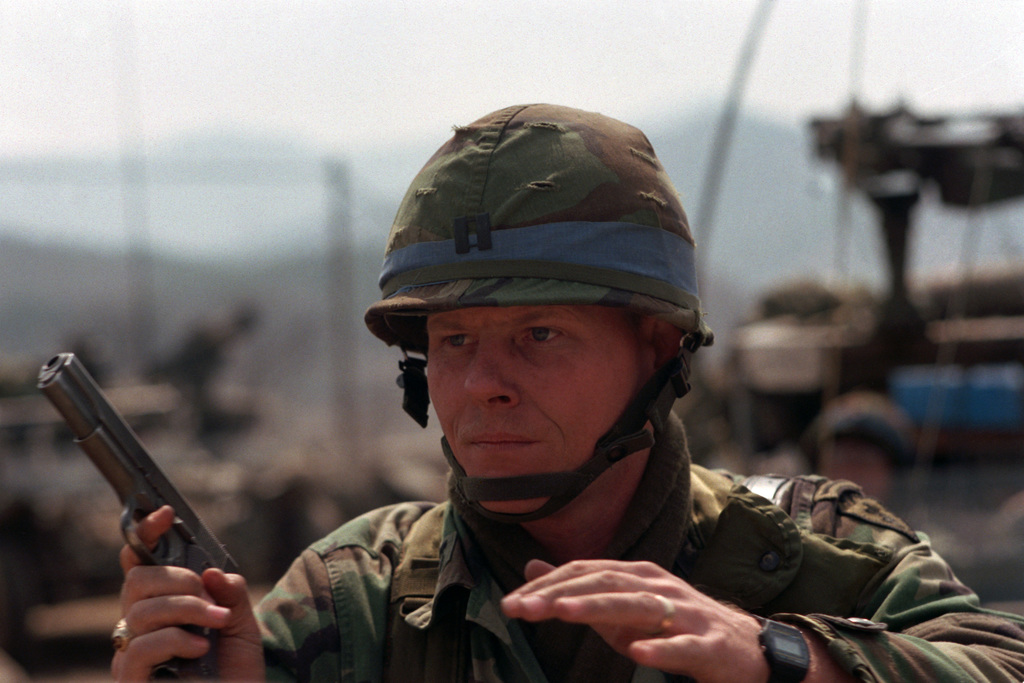 Captain (CPT) John G. Crary, battery commander, Headquarters and Service Battery, 2nd Battalion, 11th Field Artillery, 25th Infantry Division, directs the defense of a position under attack by hostile forces during the joint US/South Korean Exercise TEAM SPIRIT '86. Crary is armed with an M1911.45-caliber pistol
