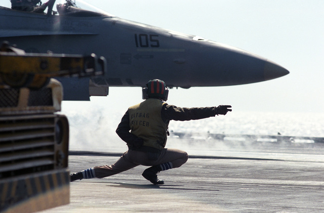 A catapult officer on the flight deck of the aircraft carrier USS CORAL SEA (CV 43) signals launching instructions to an F/A-18A Hornet pilot