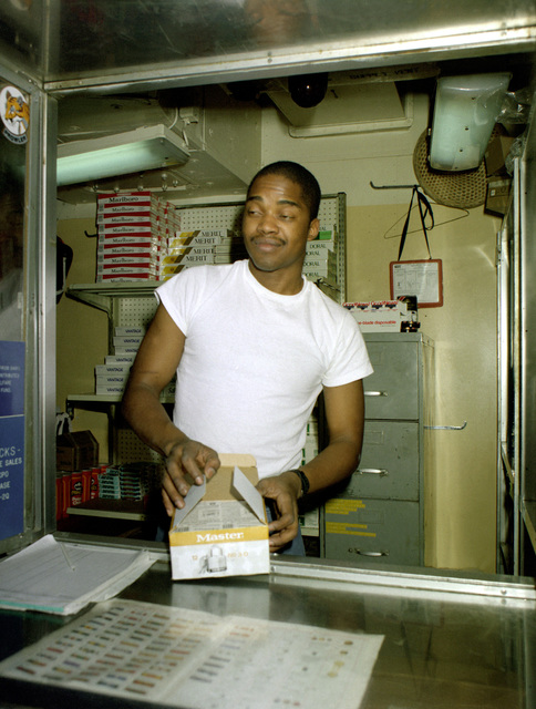A ship's serviceman aboard the aircraft carrier USS SARATOGA (CV-60) displays some of the goods for sale in one of the ship's three stores