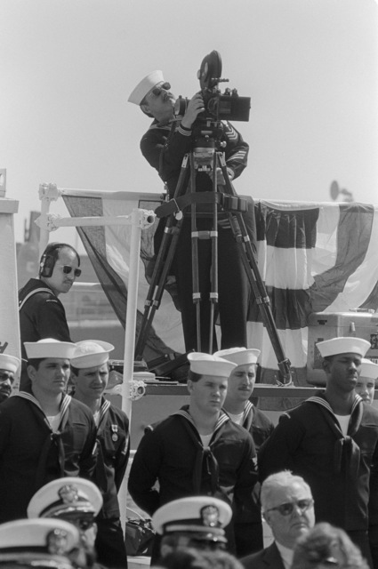A US Navy motion picture cameraman films the commissioning of the guided missile frigate USS REUBEN JAMES (FFG 57)