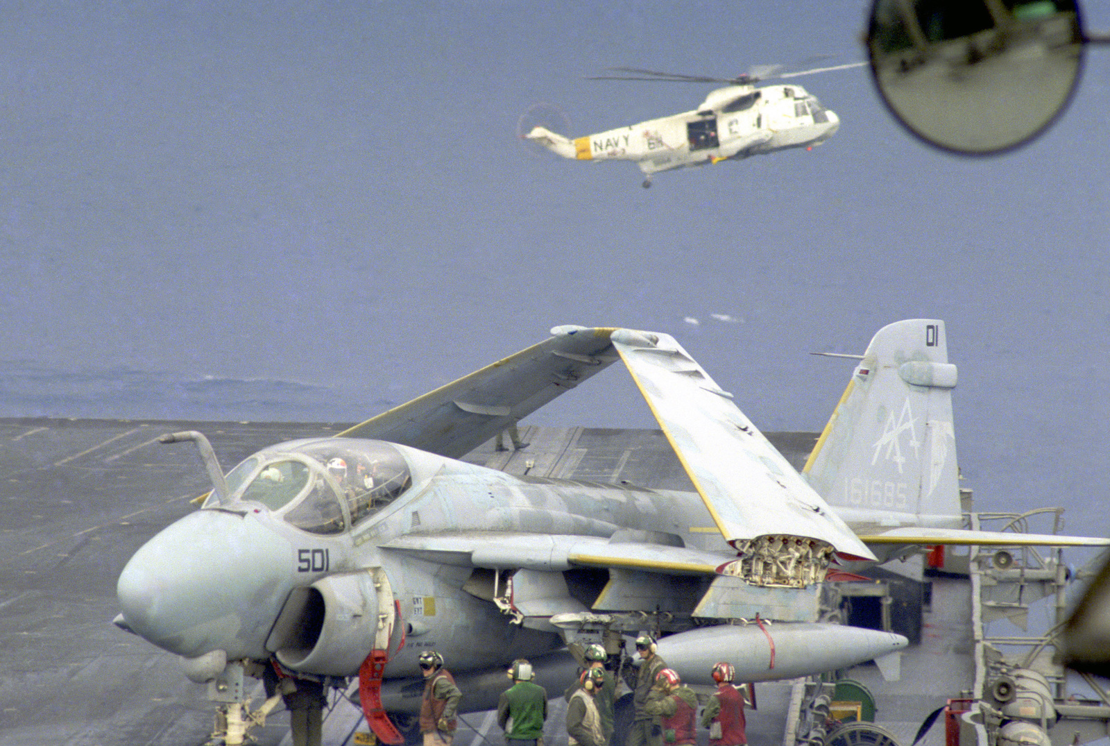 Crewmen prepare an A-6E Intruder aircraft for flight operations on the deck of the aircraft carrier USS SARATOGA (CV 60). In the background is an SH-3H helicopter