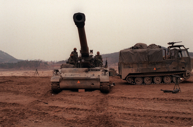 Members of Battery A, 6th Bn., 37th Field Artillery, prepare an M-110A2 8-inch howitzer for a firing mission near the South Han River during the joint U.S. and South Korean Exercise Team Spirit '86. An M-548 tracked cargo carrier is parked behind the howitzer