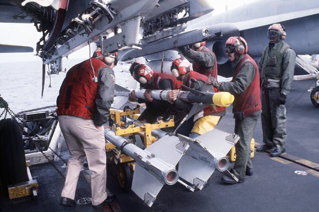 Central Mediterranean Sea.  Attack Squadron 55 (VA-55) ordnancemen lift an AIM-9L Sidewinder missile onto an underwing launch rack aboard an A6E Intruder aircraft aboard the aircraft carrier USS CORAL SEA (CV 43)
