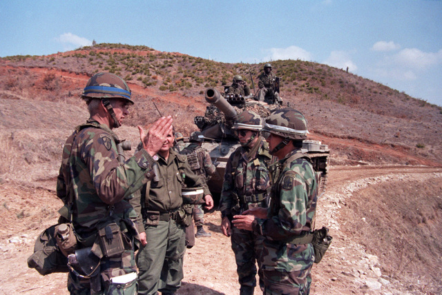 Exercise controllers from the 29th Infantry Brigade, Hawaii Army National Guard, discuss a dispute between competing forces with the commander of the 1ST Battalion, 14th Infantry Division, 25th Infantry Division, during the joint US/South Korean Exercise TEAM SPIRIT '86. In the background is an M60 tank