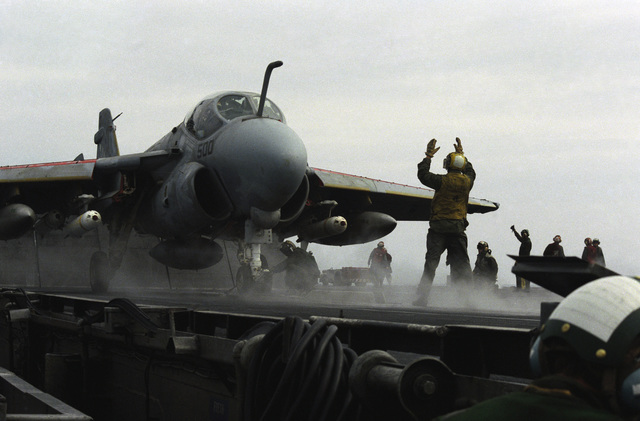 A plane director signals instructions to an A-6E Intruder aircraft pilot on the flight deck of the aircraft carrier USS SARATOGA (CV 60)