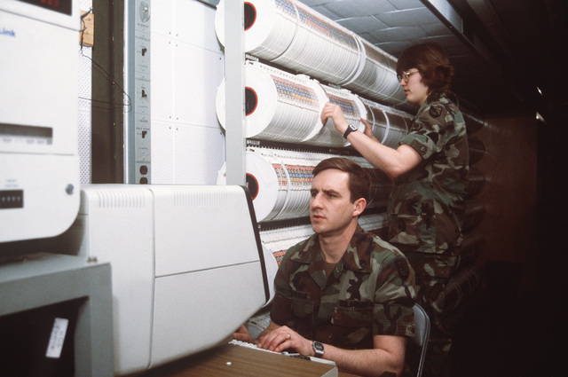 A Soldier of the 25th Data Processing Unit operates an IBM 3279 terminal while another pulls magnetic tape reels from a rack