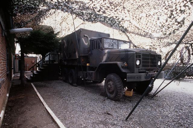 An AN/TRC-34 teletype radio center van hidden under camouflage netting alongside a building at the Edingen Transceiver Station
