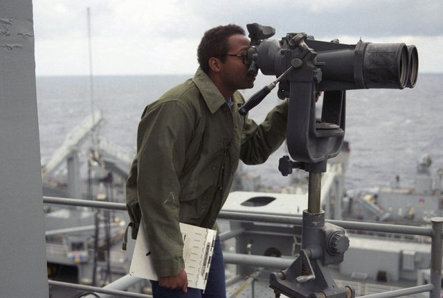 An intelligence specialist aboard the aircraft carrier USS SARATOGA (CV 60) observes a Soviet ship through high-powered binoculars as it shadows US Navy ships during an underway replenishment operation