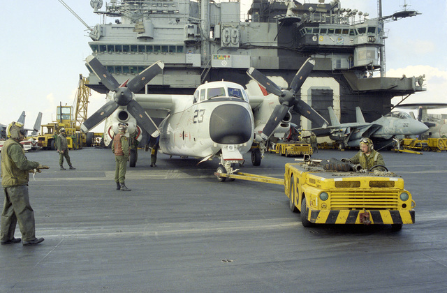 An MD-3A tow tractor is used to tow a C-2A Greyhound aircraft across the flight deck of the aircraft carrier USS SARATOGA (CV 60)