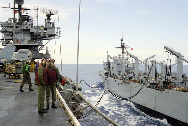 Crew members aboard the aircraft carrier USS SARATOGA (CV 60) assist in an underway replenishment operation with the fast combat support ship USS SEATTLE (AOE 3)
