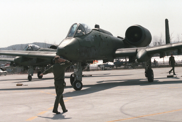 A ground crewman guides a US Air Force A-10A Thunderbolt II aircraft onto a highway for take off during the joint US and South Korean Exercise TEAM SPIRIT '86. The highway is being used by various aircraft for emergency landing training