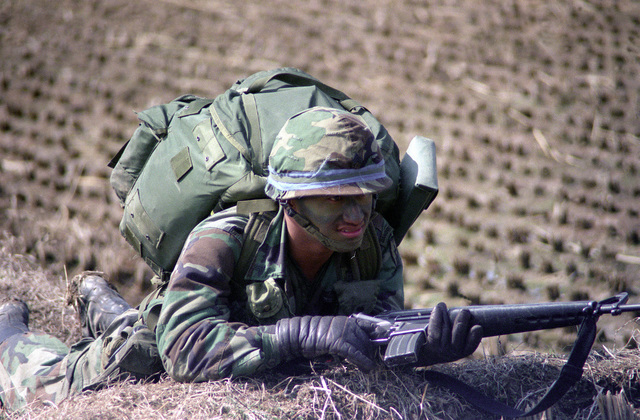 A soldier of the 1ST Bn., 35th Inf., 25th Inf. Div., takes cover in a rice paddy while participating in an air assault during the joint U.S./South Korean exercise Team Spirit '86